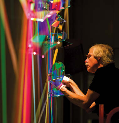 Stephen Knapp puts the final touches on his lightpainting entitled First Symphony by adjusting some of many glass elements comprising the installation.