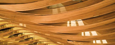 Undulating oak strips are suspended from the ceiling above the stage of the newly opened Koerner Hall in Toronto. The fluidity of the ceiling's design enhances the hall's acoustical performance and its dynamic expression.
