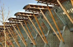 Supported by concrete buttresses, the rhythmic wooden roof elements are apparent to visitors.