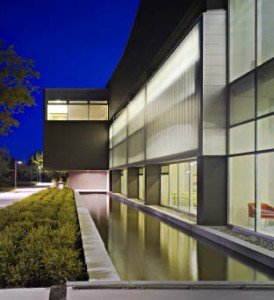 Contrasting against the dark concrete, the clear bright light emanating from the library is further accentuated by reflecting ponds along the building's perimeter.