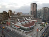 A view of the entire CBC complex illustrating the existing Brutalist concrete behemoth anchored by the new low-rise addition.
