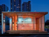 The CentrePlace Manitoba pavilion by Cibinel Architects incorporates a glazed, luminous drum form within a rectilinear frame, winning a sustainability award in the process for its use of recycled materials and reclaimed wood.