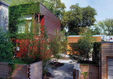 The principal house, new studio, and neighbouring garage define an urban court on this compact site.