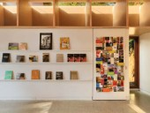North wall of the studio with its book display, bulletin board and wooden light coffers.