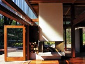 A view of the indoor/outdoor fireplace with large Douglas fir doors opening to the heavily wooded surroundings.