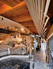 The exposed timber structure of the visitor centre is complemented by natural stone found on the rocky site, enhancing the display of artifacts and interpretive elements.