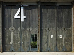 The rehabilitated doors of Barn Four create a stunning visual backdrop while reaffirming the industrial legacy of the original building.