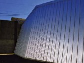 Canted aluminum cladding reflects light as a gradient tone.
