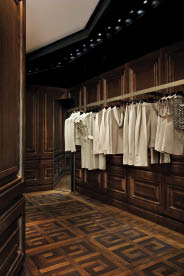 """Inside the store's autonomous fashion """"boxes,"""" customers will discover inlaid floors bearing the signature Givenchy logo as well as walls finished with rich wood panelling and painted plaster castings."""