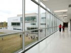 The floor-to-ceiling glazing along the classroom corridor establishes a constant connection to the site's landscape.