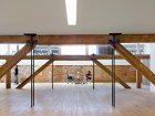 The clerestory roof supplies ample amounts of natural daylight. Original steel rods hang from a deep timber truss to support the lower floors, thus reducing the number of columns at the ground level.