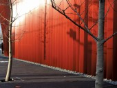 Varying light conditions change the appearance of the building's all-red exterior.