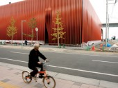 A cyclist drives by the nearly completed building.