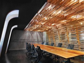 Soft light filters through a seemingly random composition of wood slats articulating the new boardroom. The impressively long table is hewn from a cherry tree felled on the millworker's own rural property.