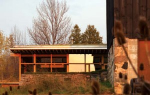 The heavy base of the stone wall anchors a generously glazed faade and an expressively horizontal floating roof.