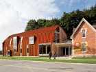 The red steel cladding complements the existing brick building and enlivens its suburban site.