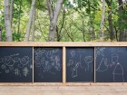 A blackboard wall forms a protective barrier between the daycare centre and the forest beyond.