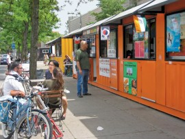 Converted shipping containers function as colourful street food stalls at the lively Scadding Court Food Market in Toronto.