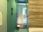 A frosted glass pane brings natural light into a shower from a private deck.