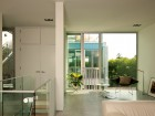 A top-floor living room gives views into the shared courtyard and a glimpse of the neighbour's kitchen.