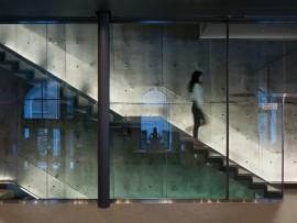 An elegantly minimalist lobby uses a palette of polished concrete, stainless steel and glass.