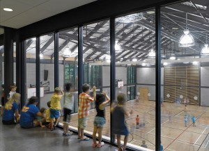 Young spectators peer into the gym from a corridor adjacent to the preschool room.
