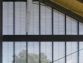 Wood louvres embedded between glass panes control solar gain and lend a fine texture to the curtain wall.