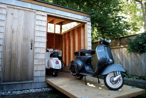 A Vespa rests on the Scooter House's lowered door, which does double duty as a work platform for the owner to indulge in his hobby.