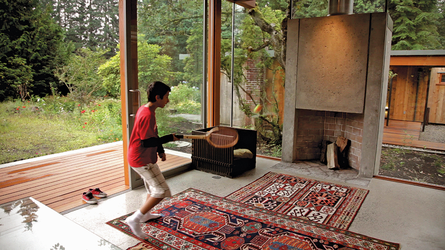 Architect Peter Pratt's son plays ball against a concrete fireplace in their West Vancouver family home. Pratt created the house as well as restoring the adjacent 1951 dwelling designed by his father, the late Ned Pratt--a seminal figure in Vancouver's architectural community. Film still, Coast Modern