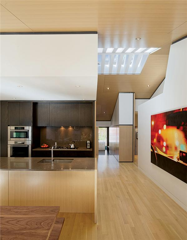 A partial view of the kitchen and the skylit corridor leading to the front entry foyer.