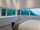 A strip of windows offers panoramic views of the ocean cove from the main bedroom.