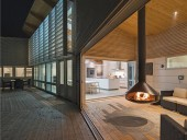 Folding glass doors fully open the lounge with its suspended wood fireplace to the outdoor deck.
