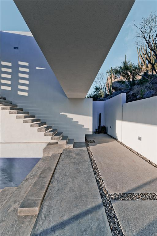 Cantilevered concrete steps lead to the bedrooms.