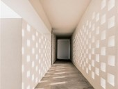 Upstairs in Z-4, a perforated wall serves as a heat sink while admitting wind and dappled light.
