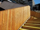 Donor names adorn the bridge's vertical wood planks. Design At News