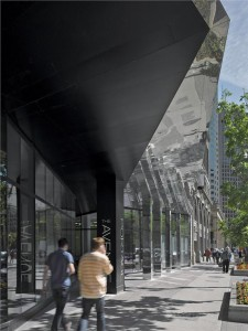 The entrance canopy shifts from stainless steel to matte black as it cuts back towards the building.