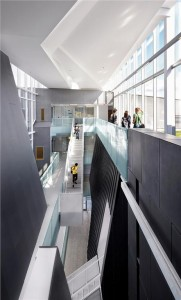 Courtyards and a green roof flank the corridor, generously daylighting two suspended stairs. Shai Gil
