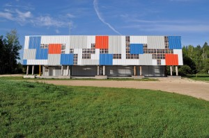 Clad with a colourful patchwork of corrugated metal and translucent polycarbonate panels, La Cuisine backstage kitchen and a companion site office were created mainly from reclaimed materials.