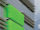 Bright green solar shutters on the south faade pivot to block excess sunlight.