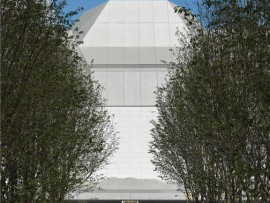 The auditorium roof of the Aga Khan Museum rises at the end of an avenue of serviceberry trees.