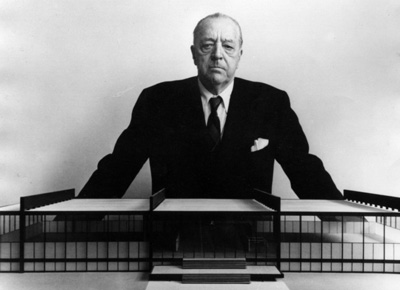 mies van der rohe standing over a model of crown hall