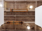 Vestiges of the building's prior industrial life are evident in the orange jib cranes affixed to the wood ceiling beams at the Equinox. Latreille Delage Photography
