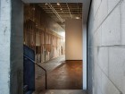 A view from the rear office area at Monte Clark into the main space reveals a grove of wooden dowels along the entire east wall comprising the open storage system for the gallery's collection. silentSama Architectural Photography