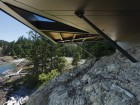 A view of the building's underbelly demonstrates how the steel structure anchors the cantilevered mass of the house to the rocky site.