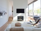 Three steps and a fireplace separate the living room from the dining room, while a flanking set of sliding glass doors encourages a sense of continuity between the spaces.