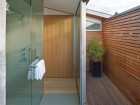 Glass doors open the shower and tub areas to a screened rooftop patio for a spa-like bathing experience.