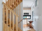 A solid wood central stair threads together the two-storey house with its basement utility room.