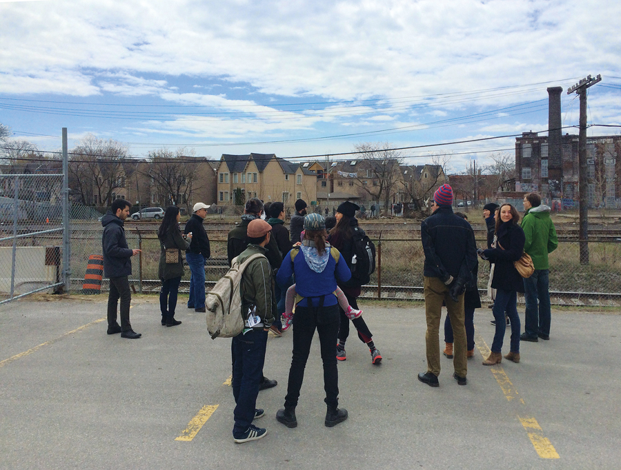 On a recent tour led by regionalArchitects, locals examine the site of a future bridge, planned as part of the West Toronto Railpath's second phase.  Sandrina Dumitrascu