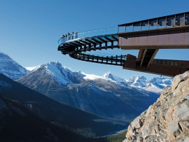 The Skywalk's glass-floored walkway is visually counterbalanced by massive Corten steel arms that connect to the rock face. Brewster Travel Canada