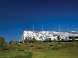 Sited at the edge of the SAIT campus in downtown Calgary, a new parkade uses punched metal panels to create a shiny image of moving clouds on its facades. Nic Lehoux